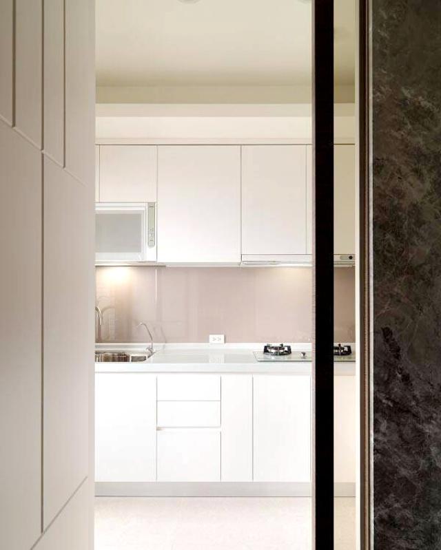 现代简约的深色烤漆橱柜与白色台面对比鲜明,使整个厨房干净整洁。