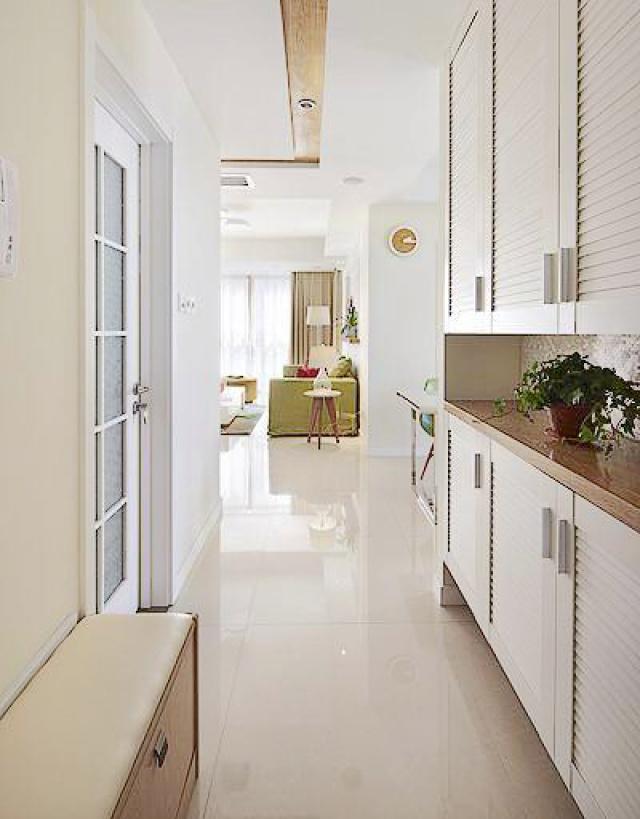 从玄关往里面望,右边是整面墙的储物柜,左边摆放了一个低矮的鞋柜。