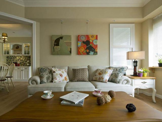 悬挂式壁画既能装饰墙面,又容易清洁打理。沙发选用偏向美式乡村风格的卷边沙发,放上小碎花靠枕。