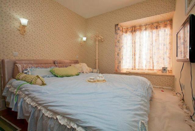 主卧比较简单,木质板床和大花的壁纸。